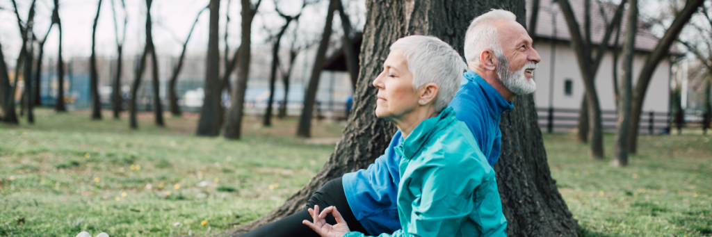Older couple, a man and a woman both stretching and meditating. They have blue jumpers and black long pants on and have grey hair.